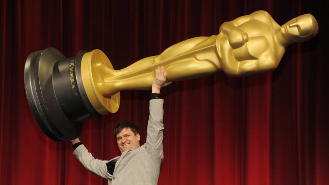 """Filmmaker John Mattiuzzi of the School of Visual Arts in New York, a nominee in the Alternative Category for his film """"The Compositor,"""" hoists up an Oscar statue for photographers before the Academy of Motion Picture Arts and Sciences 40th Student Academy Awards at the Samuel Goldwyn Theater on Saturday, June 8, 2013 in Beverly Hills, Calif. (Photo by Chris Pizzello/Invision/AP)"""