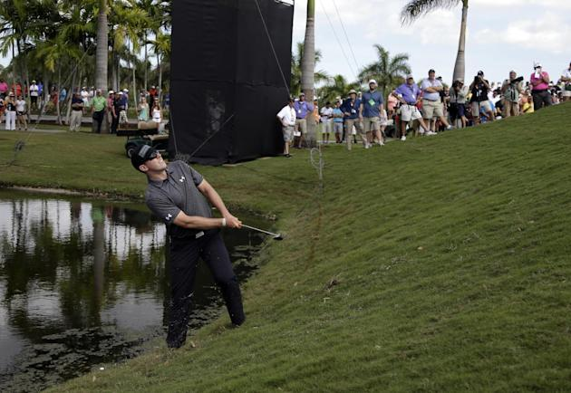 Hunter Mahan hits onto the fifth green after hitting his ball into the water during the final round of the Cadillac Championship golf tournament Sunday, March 9, 2014, in Doral, Fla. (AP Photo/Lynne S