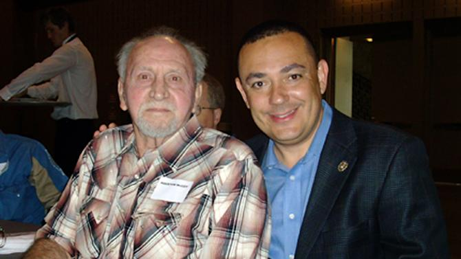 In this April 21, 2010 photo provided by the Austin Police Department, retired APD officer Houston McCoy, left, poses with police chief Art Acevedo, right, in Austin, Texas.  McCoy, the Austin police officer who helped stop Charles Whitman's 1966 sniper rampage from atop the University of Texas tower, has died. He was 72. (AP Photo/Austin Police Department, File)