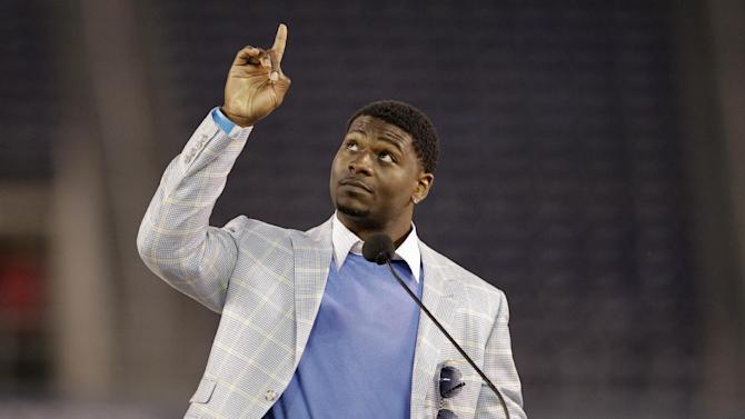Former San Diego Chargers running back LaDainian Tomlinson points upward during a public memorial service for the late NFL football player Junior Seau at Qualcomm Stadium Friday, May 11, 2012, in San Diego. Seau committed suicide on May 2 at his Oceanside, Calif., home. He played parts of 20 seasons in the NFL, with the San Diego Chargers, Miami Dolphins and New England Patriots. (AP Photo/ Gregory Bull)