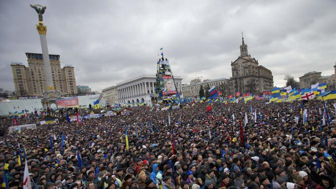 Pro-European Union activists gather during a rally in the Independence Square in Kiev, Ukraine, Sunday, Dec. 8, 2013. Over 200,000 angry Ukrainians occupied a central Kiev square on Sunday, to denounce President Viktor Yanukovych's decision to turn away from Europe and align this ex-Soviet republic with Russia, as massive protests continued for a third week. (AP Photo/Alexander Zemlianichenko)