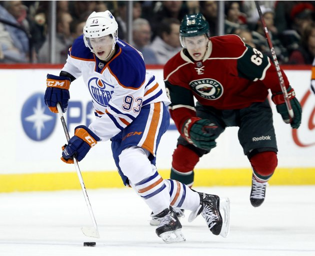 Edmonton Oilers center Ryan Nugent-Hopkins brings the puck up ice ahead of Minnesota Wild center Charlie Coyle