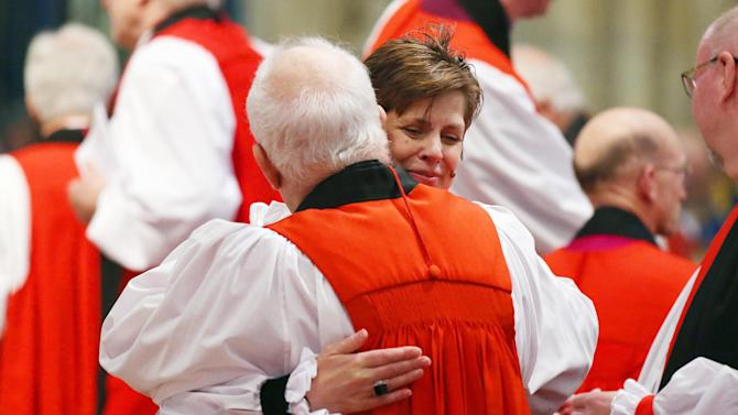 The Reverend Lane hugs a member of the clergy during a service where she was consecrated as the first female Bishop in the Church of England at York Minster in York, northern England