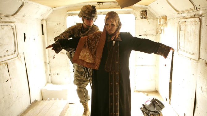 FILE - In this Sunday, April 12, 2009, file photo, an Iraqi woman is searched by a female U.S. soldier before reuniting with her husband, who was among 32 men released from U.S. military detention at Camp Bucca to their families in Tarmiyah, 50 kilometers (30 miles) north of Baghdad, Iraq, (AP Photo/Maya Alleruzzo, File)