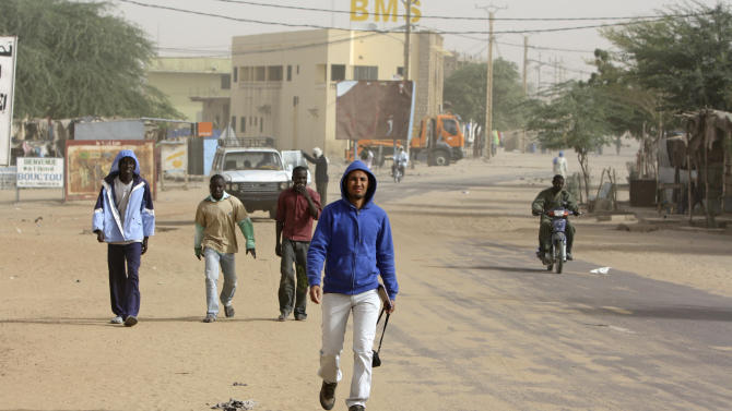 In this image taken on Saturday Jan. 31, 2013, Baba Ahmed, 26, AP's correspondent in Bamako walks down a street in Timbuktu, Mali. In Baba Ahmed's own words, not a single light could be seen in my hometown of Timbuktu as we approached it at night just days after it was liberated from the al-Qaida-linked militants who ruled for nearly 10 months. The last time Baba had visited was in May, a month after the Islamic rebels seized Timbuktu. After my visit I covered my hometown's plight for The Associated Press from the distant capital of Bamako, straining for information over the telephone each week about what had become of this city I love.  (AP Photo/Harouna Traore)