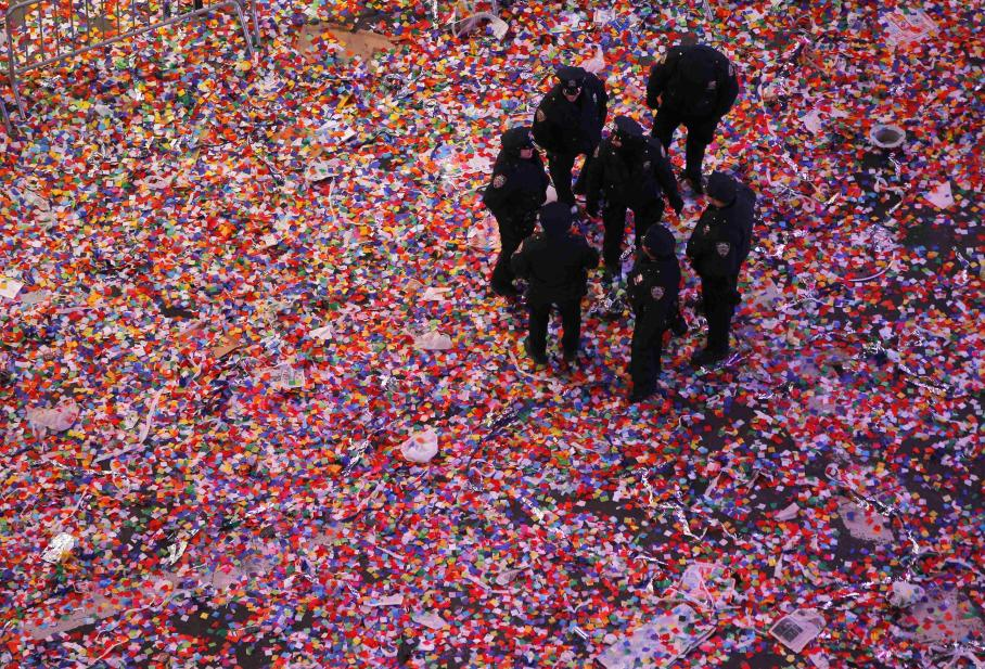 Police officers stand in confetti after it was dropped on revelers at midnight during New Year's Eve celebrations in Times Square in New York