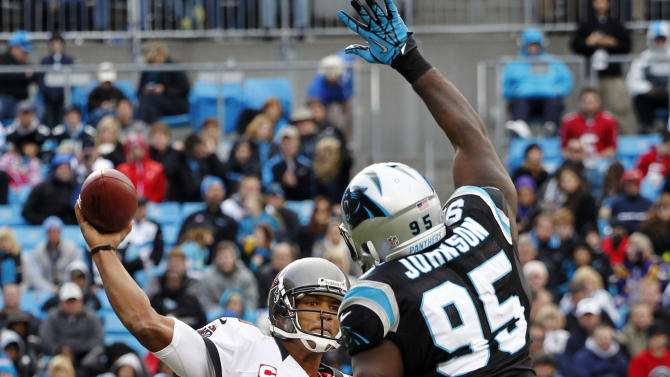 Tampa Bay Buccaneers quarterback Josh Freeman (5) throws a pass under pressure from Carolina Panthers' Charles Johnson (95) during the second half of an NFL football game in Charlotte, N.C., Sunday, Nov. 18, 2012. (AP Photo/Bob Leverone)