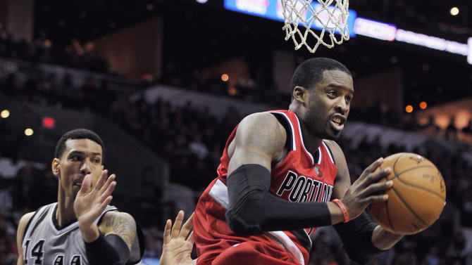 Portland Trail Blazers guard Wesley Matthews, right, looks to pass after driving past San Antonio Spurs' Danny Green, left, and Tim Duncan during the second half of an NBA basketball game, Friday, Dec. 19, 2014, in San Antonio. Portland won 129-119 in triple overtime. (AP Photo/Darren Abate)