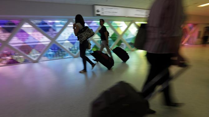 "In this Thursday, Sept. 27, 2012 photo, passengers travel through an airport in Miami. Private researchers, who have analyzed federal data on airline performance, say in a report being released Monday, April 8, 2013, that consumer complaints to the Department of Transportation surged by one-fifth last year even though other measures such as on-time arrivals and mishandled baggage show airlines are doing a better job. ""The way airlines have taken 130-seat airplanes and expanded them to 150 seats to squeeze out more revenue I think is finally catching up with them,"" says Dean Headley, a business professor at Wichita State University, who has co-written the annual report for 23 years. (AP Photo/Lynne Sladky)"