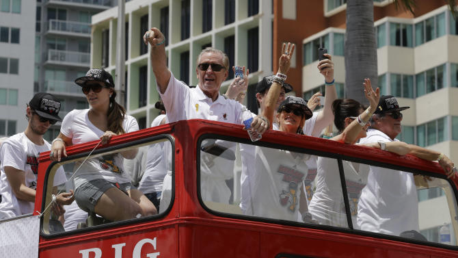 NBA champion Miami Heat president Pat Riley, center, points to fans during a parade honoring the team in Miami, Monday, June 24, 2013. (AP Photo/Alan Diaz)