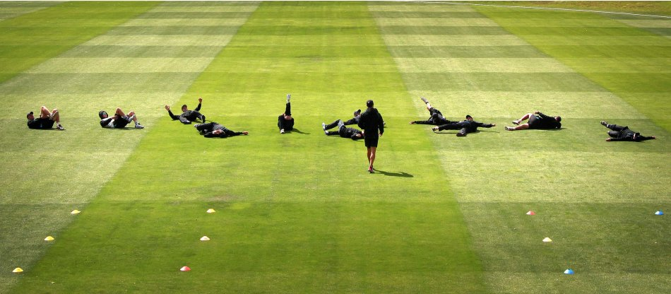 Members of the New Zealand cricket team stretch before the start of a training session at the University Oval in Dunedin