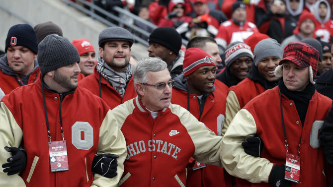 Former Ohio State head coach Jim Tressel gathers with members of his 2002 national championship team between quarters of an NCAA college football game between Ohio State and Michigan Saturday, Nov. 24, 2012, in Columbus, Ohio. (AP Photo/Mark Duncan)