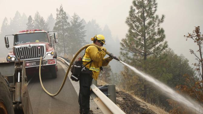 Firefighters battle the King Fire along Highway 50, northeast of Sacramento, California