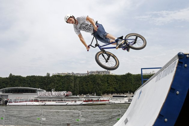 A rider practices BMX on a ramp on the opening day of the new pedestrian walkway area between Orsay museum and Alma bridge on the left bank of the River Seine in Paris