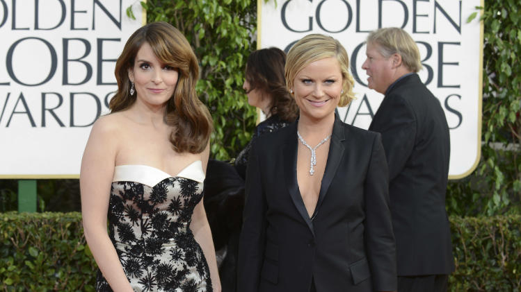 Show hosts Tina Fey, left, and Amy Poehler arrive at the 70th Annual Golden Globe Awards at the Beverly Hilton Hotel on Sunday Jan. 13, 2013, in Beverly Hills, Calif. (Photo by Jordan Strauss/Invision/AP)