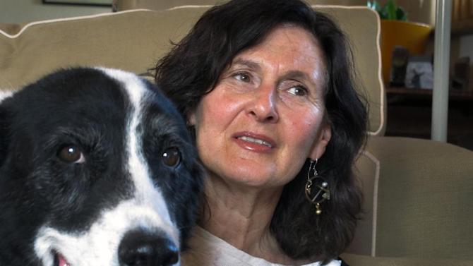 """In this March 19, 2013 photo, Heidi Schulman poses for a photo with her rescue dog, Bosco, in Santa Fe, N.M. Bosco inspired her to develop """"The Original Dog Tarot: Divine the Canine Mind,"""" to help people better connect with their pets. It's an age-old and seemingly answerless question: What in the world is my dog thinking? It has generated a growing market of scientific research, radio and television shows, books by pet psychics, even pet tarot cards. (AP Photo/Jeri Causing)"""
