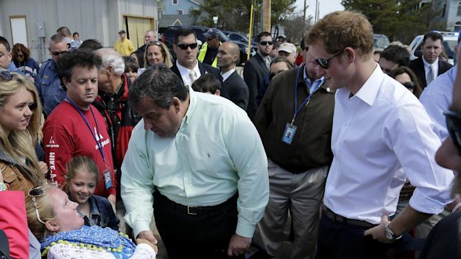 New Jersey Gov. Chris Christie, center, talks to a resident as Britain's Prince Harry, right, looks on while visiting the area hit by Superstorm Sandy, Tuesday, May 14, 2013, in Seaside Heights, N.J.  Prince Harry began a tour  of New Jersey's storm-damaged coastline, inspecting dune construction, walking past destroyed homes and shaking hands with police and other emergency workers.  New Jersey sustained about $37 billion worth of damage from the storm. (AP Photo/Mel Evans, Pool)
