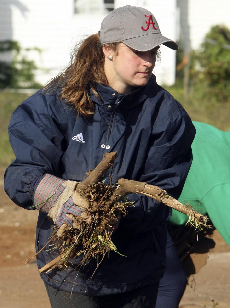 In this photo taken Oct. 19, 2011,  Notre Dame lacrosse player Adele Bruggeman picks up tornado debris in Tuscaloosa, Ala. Twenty-four student athletes from Notre Dame were in Tuscaloosa volunteering time during their fall break to help clean up tornado damaged areas. (AP Photo/The Tuscaloosa News, Robert Sutton)
