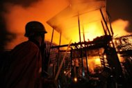 <p>Firemen are seen extinguishing a fire engulfing houses in Sittwe, capital of the western state of Rakhine, on June 15. Fifty people have been killed and scores wounded in fresh communal clashes in the restive area, according to state media.</p>