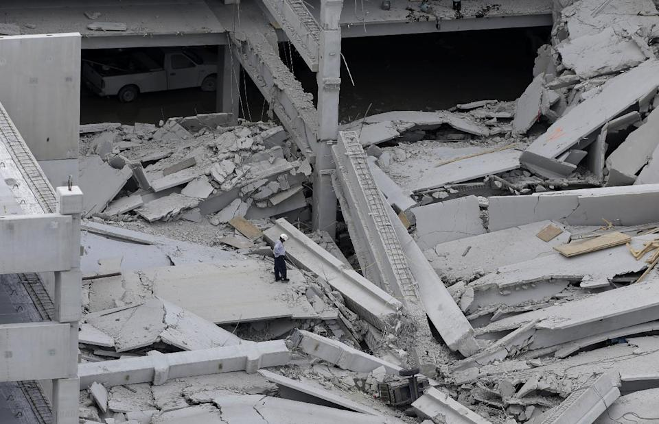 A rescue worker walks through the rubble at a five-story parking garage after it collapsed at Miami-Dade College, Wednesday, Oct. 10, 2012 in Miami, killing one worker and trapping two others in the rubble, officials said. Several other workers were hurt, including one rescued from the debris. (AP Photo/Lynne Sladky)
