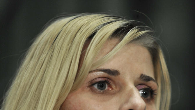 Bartender Karolina Obrycka listens while her attorney Terry Ekl speaks during a news conference in Chicago on Tuesday, Nov. 13, 2012.  Jurors awarded $850,000 in damages to Obrycka, who was beaten in February 2007 by off-duty Chicago police officer Anthony Abbate, who was admittedly drunk at the time.  Surveillance video of the hulking Abbate pushing Obrycka to the ground behind the bar at Jesse's Shortstop Inn, then repeatedly punching and kicking her went viral online. (AP Photo/Paul Beaty)
