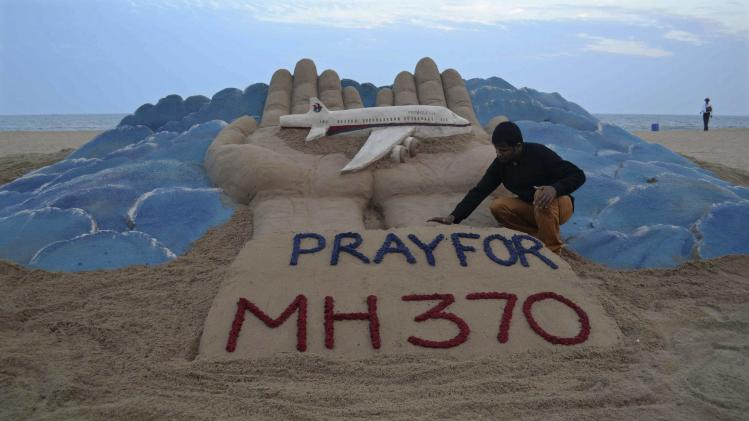 Indian sand artist Pattnaik works on a sand sculpture of missing Malaysian Airlines flight MH370, at golden beach at Puri in the eastern Indian state of Odisha