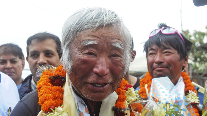 80-year-old Japanese climber Yuichiro Miura, who became the oldest conqueror of Mount Everest on Thursday, is garlanded as he returns from camp 2 by helicopter in Katmandu, Nepal, Sunday, May 26, 2013. Miura, a Japanese former extreme skier, told reporters at Katmandu's airport that he was happy to have set a new record for oldest climber. He scaled the 8,850-meter (29,035-foot) peak on Thursday. A competitor, Nepal's Min Bahadur Sherchan, 81, is still on the mountain hoping to break Miura's record. On the right is son Gota Miura,(AP Photo/Bikash Dware)