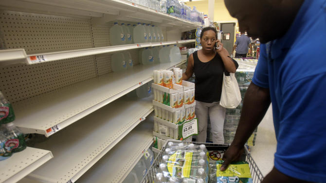 Shoppers stock up on water from rapidly emptying shelves at a grocery store in Far Rockaway in New York, Thursday, Aug. 25, 2011.  Mayor Michael Bloomberg on Thursday urged New York City residents living in low-lying areas to line up a place to stay on high ground ahead of a possible evacuation this weekend due to Hurricane Irene. (AP Photo/Seth Wenig)