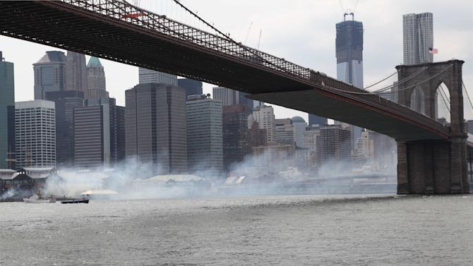 Smoke rises off Pier 17 and floats along the East River toward the Brooklyn Bridge as firefighters fight a three alarm blaze at the South Street Seaport, Saturday, July 14, 2012, in New York. About 140 firefighters and the U.S. Coast Guard responded to the blaze that broke out about 4 p.m. Saturday. There were no injuries. (AP Photo/Lisa Tolin)