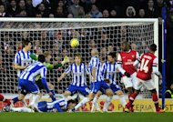 Arsenal's Theo Walcott (R) scores their third goal during their 3-2 FA Cup fourth round win over Brighton & Hove Albion at The American Express Community Stadium in Brighton, on January 26, 2013
