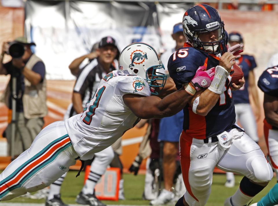 Miami Dolphins outside linebacker Cameron Wake (91) tackles Denver Broncos quarterback Tim Tebow (15) during the first half of an NFL football game Sunday, Oct. 23, 2011, in Miami. (AP Photo/Hans Deryk)