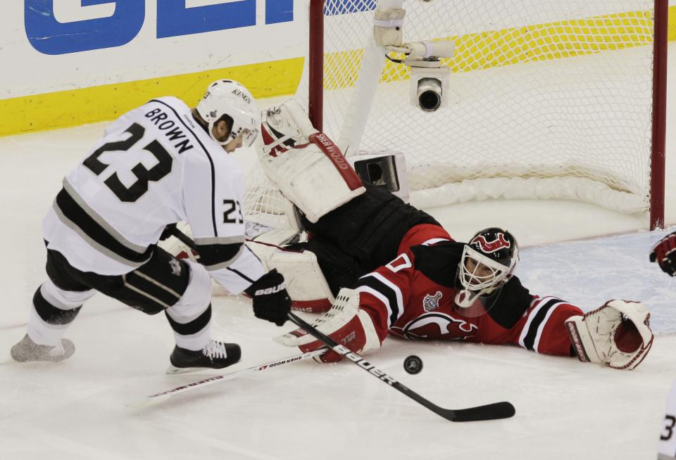 New Jersey Devils' Martin Brodeur reaches to stop the puck as Dustin Brown approaches in the first period during Game 5 of the NHL hockey Stanley Cup finals, Saturday, June 9, 2012, in Newark, N.J.. (AP Photo/Peter Morgan)
