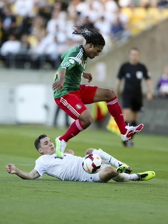Mexico's Carlos Pena leaps over New Zealand's Storm Roux during their World Cup qualifying soccer match at Westpac Stadium, in Wellington, New Zealand, Wednesday, Nov. 20, 2013. Mexico qualified for t