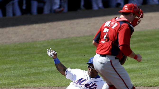 New York Mets non-roster invitee outfielder Marlon Byrd (6) slides in with a run past Washington Nationals catcher Chris Snyder (7) on an RBI single by Jordany Valdespin during the fourth inning of an exhibition spring training baseball game in Port St. Lucie, Fla., Saturday, Feb. 23, 2013, in (AP Photo/Julio Cortez)