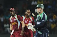West Indies cricketer Chris Gayle (C) celebrates with his captain Darren Sammy (L) after he dismissed Ireland cricketer Niall O&#39;Brien (R) during the ICC Twenty20 Cricket World Cup match between West Indies and Ireland at the R. Premadasa Stadium in Colombo. The West Indies qualified for the Super Eights stage of the World Twenty20 after the match against Ireland was abandoned due to rain