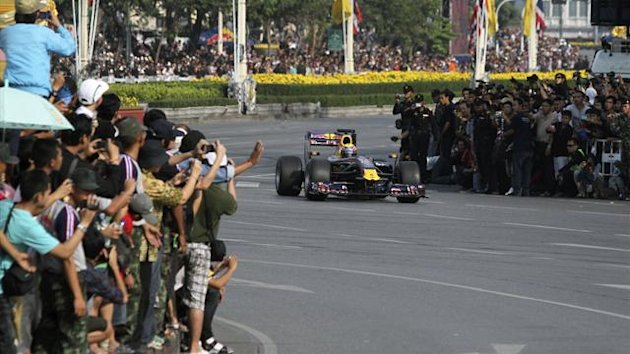 A Red Bull Formula One race car drives on Rajdamnoen Avenue, as part of the celebrations for Thailand's King Bhumibol Adulyadej's 83rd birthday (Reuters)