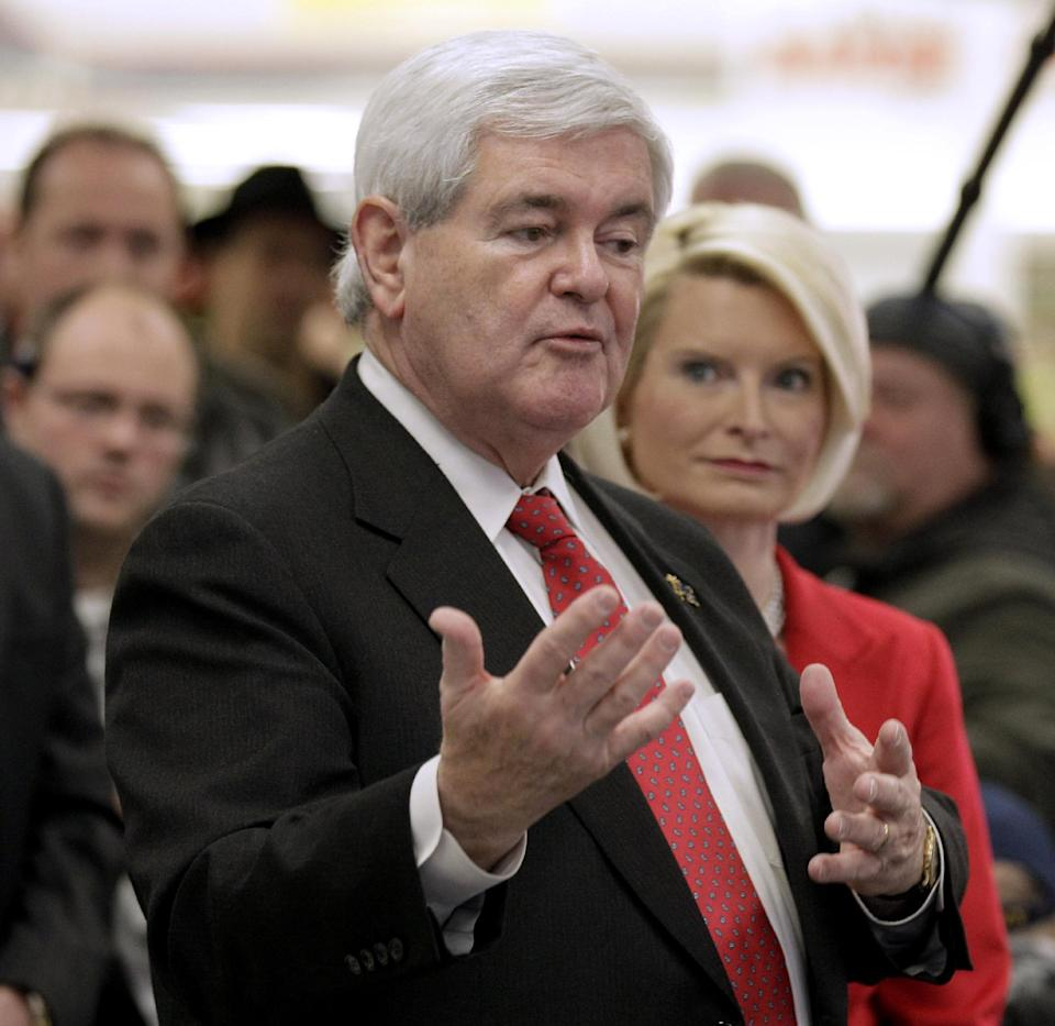 Republican presidential hopeful, former House Speaker Newt Gingrich, with his wife Callista, speaks at a Hy-Vee store in Mt Pleasant, Iowa, Tuesday, Dec. 20, 2011. (AP Photo/Charlie Riedel)