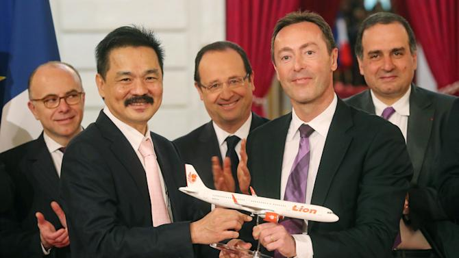FILE - In this Monday, March 18, 2013 file photo, Lion Air President and chief executive Rusdi Kirana of Indonesia, second left, and Airbus President and chief executive Fabrice Bregier, second right, pose with an Airbus 320 model for the media while France's President Francois Hollande, center, applauds with others during a signing ceremony at the Elysee Palace in Paris when the Indonesian airline announced to buy 234 Airbus plane for 18.4 billion Euro ($24 billion). Indonesia's top discount carrier, which catapulted into the global aviation spotlight with record deals to buy Airbus and Boeing planes, is taking the battle for Asia's budget-minded travelers to the backyard of the airline that helped pioneer low cost flights in the region. (AP Photo/Michel Euler, File)