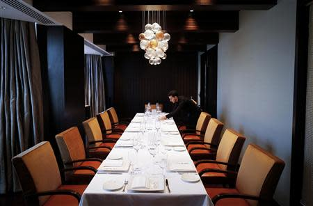 An employee of Le Cirque Signature restaurant prepares a table inside a private dining room in Mumbai