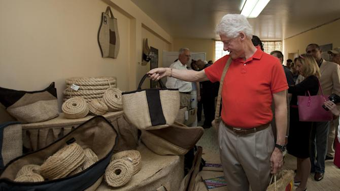 Former U.S. President and UN special envoy to Haiti, Bill Clinton looks at bags and ropes made out of sisal fiber during a visit to the sisal fiber production company Sisalco S.A. in Port-au-Prince, Haiti. Monday March. 11, 2013. (AP Photo/Dieu Nalio Chery)
