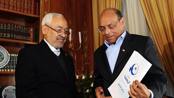 Tunisian President Moncef Marzouki, right, receives a letter regarding the appointment of Interior Minister Ali Larayedh to succeed outgoing Prime Minister Hamadi Jebali from Ennahda ruling party's leader Rached Ghannouchi prior to a meeting at the presidential palace in Carthage near Tunis, Friday, Feb. 22, 2013. Tunisian President Moncef Marzouki on Friday has asked incumbent Interior Minister Ali Laarayedh from the ruling Ennahdha to form a new government in two weeks, according to the presidential office. (AP Photo/Hassene Dridi)