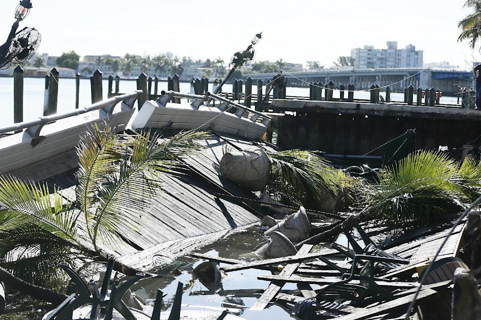 A collapsed deck sits in the water Friday, June 14, 2013, after it collapsed at Shuckers Bar and Restaurant, in Miami. The packed outdoor deck behind the popular sports bar partially collapsed during the NBA Finals on Thursday night, sending dozens of patrons into the shallow waters of Biscayne Bay. (AP Photo/J Pat Carter)