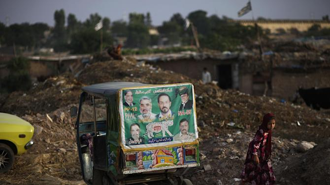 """A Pakistani girl, right, who was displaced with her family from Pakistan's tribal areas due to fighting between militants and the army, walks past an election banner showing former prime minister and leader of Pakistan Muslim League-N, Nawaz Sharif, and other members of his party, pasted on a rickshaw parked in a poor neighborhood on the outskirts of Islamabad, Pakistan, Monday, May 13, 2013. Nawaz Shari, the Pakistani politician poised to become the country's next prime minister said Monday that Islamabad has """"good relations"""" with the United States, but called the CIA's drone campaign in the country's tribal region a challenge to national sovereignty. (AP Photo/Muhammed Muheisen)"""
