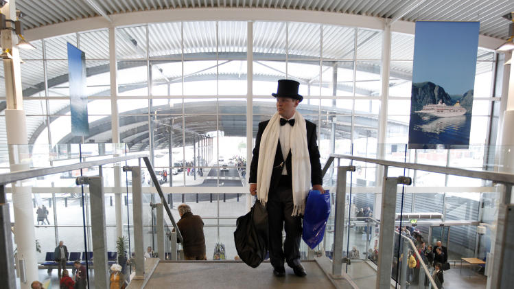 A passenger in evening dress  hurries as he goes to check in for the MS Balmoral Titanic memorial cruise in Southampton, England, Sunday, April  8, 2012. Nearly 100 years after the Titanic went down, a cruise with the same number of passengers aboard is setting sail to retrace the ship's voyage, including a visit to the location where it sank. The Titanic Memorial Cruise is set to depart Sunday from Southampton, where the Titanic left on its maiden voyage. The 12-night cruise will commemorate the 100th anniversary of the sinking of the White Star liner. With 1,309 passengers aboard, the MS Balmoral will follow the same route as the Titanic. Organizers are trying to recreate the onboard experience  minus the disaster  from the food to a band playing music from that era. Organizers said people from 28 countries have booked passage, including relatives of some of the more than 1,500 people who died when the Titanic collided with an iceberg and sank on April 15, 1912.(AP Photo/Alastair Grant)