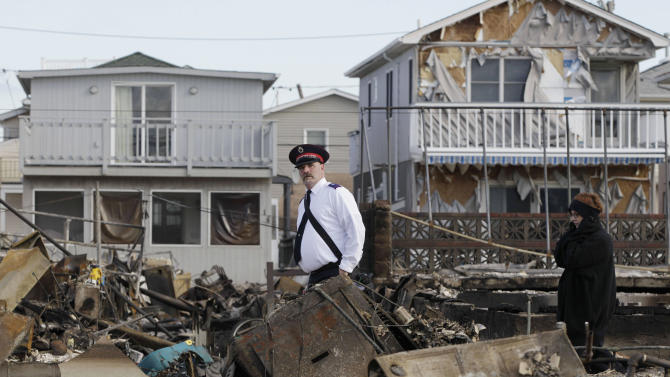 A representative of the Salvation Army walks past homes destroyed by Superstorm Sandy in Breezy Point, Sunday, Nov. 4, 2012, in New York. The beachfront neighborhood heavy populated by firefighters and police officers was devastated during the storm when a fire pushed by Sandy's raging winds destroyed 100 or more homes and buildings. (AP Photo/Kathy Willens)