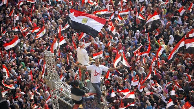 """Opponents of Egypt's Islamist President Mohammed Morsi shout slogans and wave a national flags in Tahrir Square in Cairo, Egypt, Wednesday, July 3, 2013. Arabic reads, """" leave."""" The deadline on the military's ultimatum to President Mohammed Morsi has expired, with 48 hours passing since the time it was issued. Giant cheering crowds of Morsi's opponents have been gathered in Cairo's Tahrir Square and other locations nationwide, waving flags furiously in expection that the military will act to remove the Islamist president after the deadline ends. (AP Photo/Amr Nabil)"""