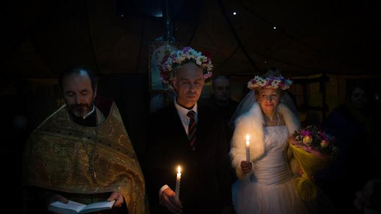 A priest celebrates a marriage under a tent on Independence square in Kiev on February 14, 2014