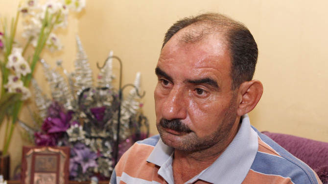 """In this Saturday, Sept. 1, 2012 photo, Waleed Abdul-Wahid is interviewed in Baghdad, Iraq after his family's return from Syria. Abdul-Wahid and his family decided to return to Iraq when masked gunmen broke into the small apartment on the Syrian capital's outskirts where his family had lived peacefully for nearly three years. The gunmen shouted, """"Are you Sunni or Shiite?"""" (AP Photo/Karim Kadim)"""