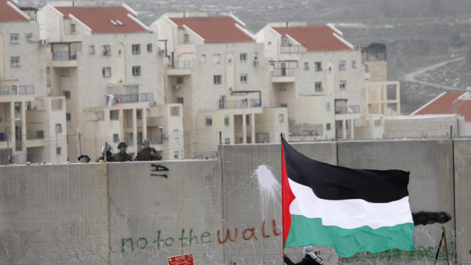 """ADVANCE FILE - In this Feb. 17, 2012 file photo a protestor waves a Palestinian flag in front of Israeli troops during a protest against Israel's separation barrier in the West Bank village of Bilin, near Ramallah. A film made by Bilin resident and amateur filmmaker Emad Burnat has been shortlisted for an Oscar. The film """"5 Broken Cameras,"""" features footage shot by Burnat, who bought a camera to film home videos but ended up documenting six years of family life on the backdrop of weekly Palestinian demonstrations against the building of Israel's separation barrier through Bilin. Two Israeli-produced documentaries about the conflict have been shortlisted for nomination in this year's Academy Awards. (AP Photo/Majdi Mohammed)"""