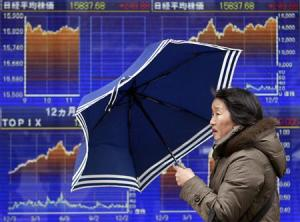 A pedestrian holding an umbrella walks past an electronic board displaying graphs of the recenent movement of Japan's Nikkei average outside a brokerage in Tokyo